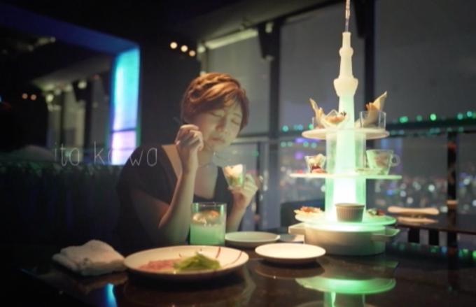 夜景の綺麗な所で食事をしている女性