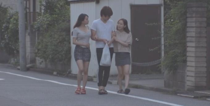 腕を組んで道を歩いている男女3人