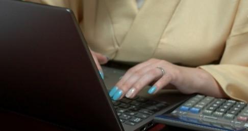 パソコンと電卓を使っている女性