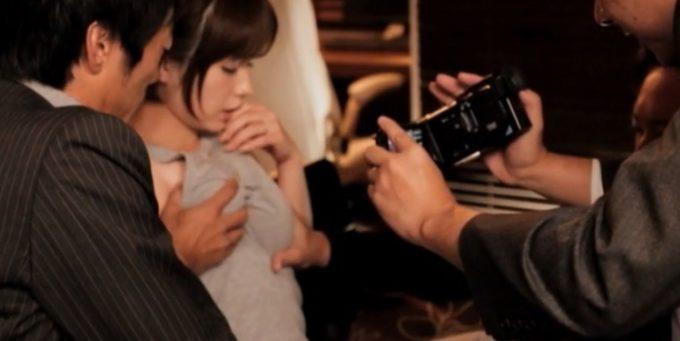 女性の胸を触っている男性をカメラで撮影している男性