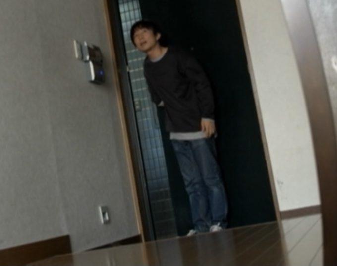 玄関で在宅を確かめる男